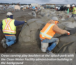 Crews carving play boulders at the splash park with the Clean Water Facility administration building in the background