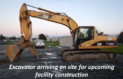 Excavator arriving on site for upcoming facility construction