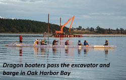 Dragon boaters pass the excavator and barge in Oak Harbor Bay