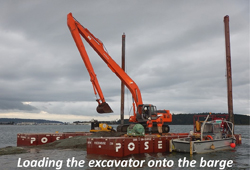 Outfall pipe installation in tidal flat and construction barge in Oak Harbor Bay