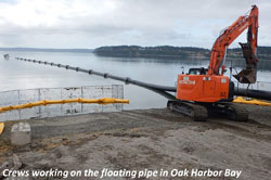 Crews working on ght floating pipe in Oak Harbor Bay
